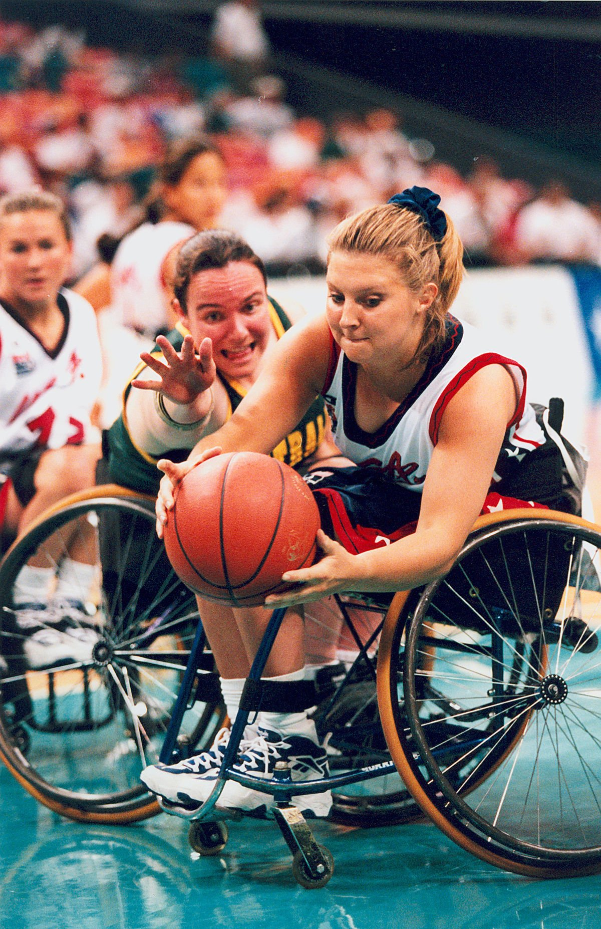 Two women in wheelchairs playing basketball