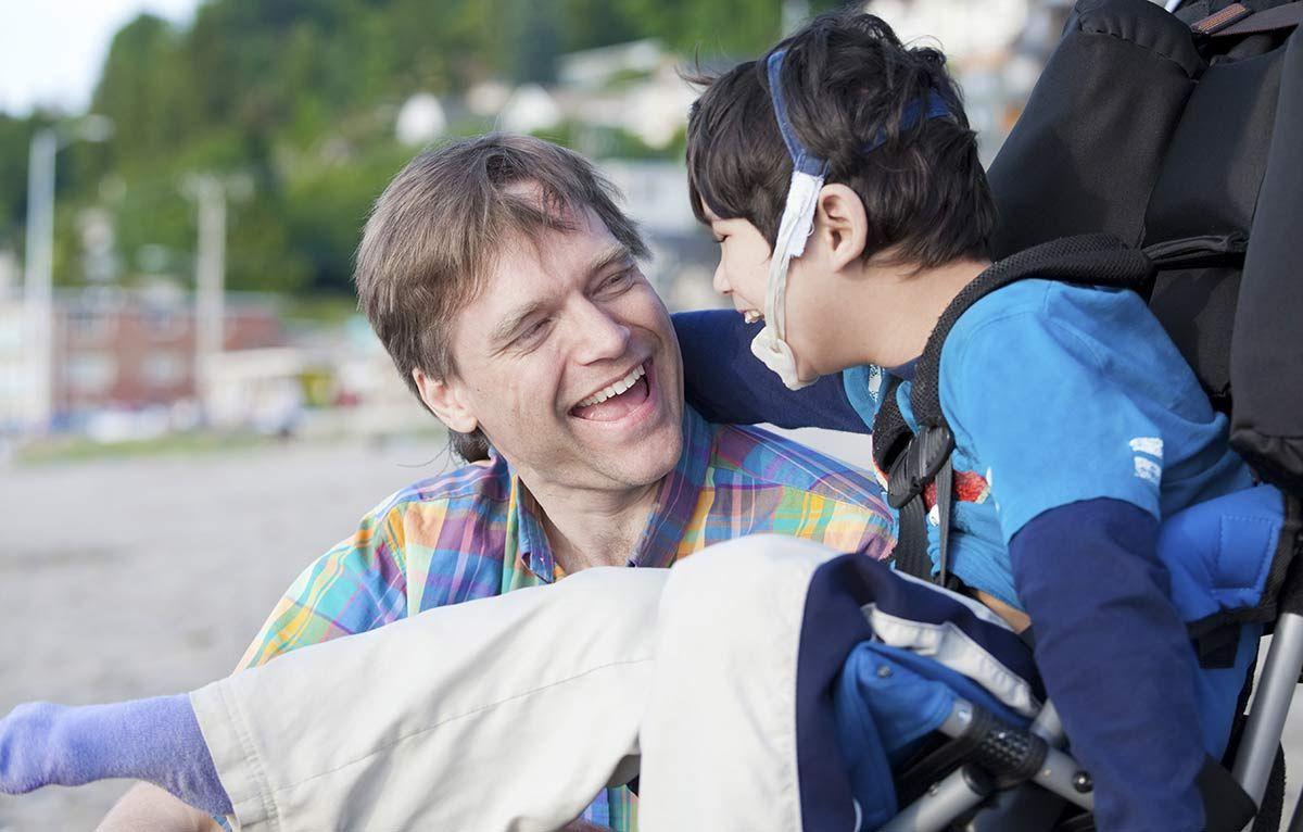 Man holding disabled boy